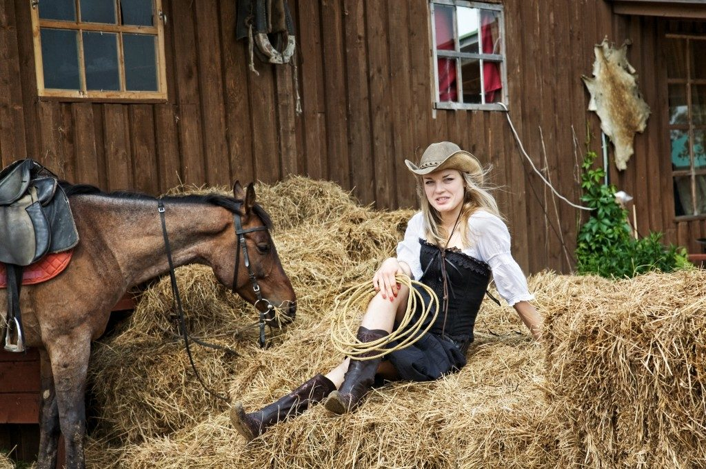 Cowgirl sitting on the hay