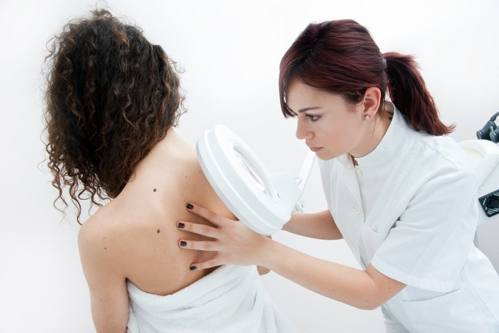Doctor inspecting the woman's skin