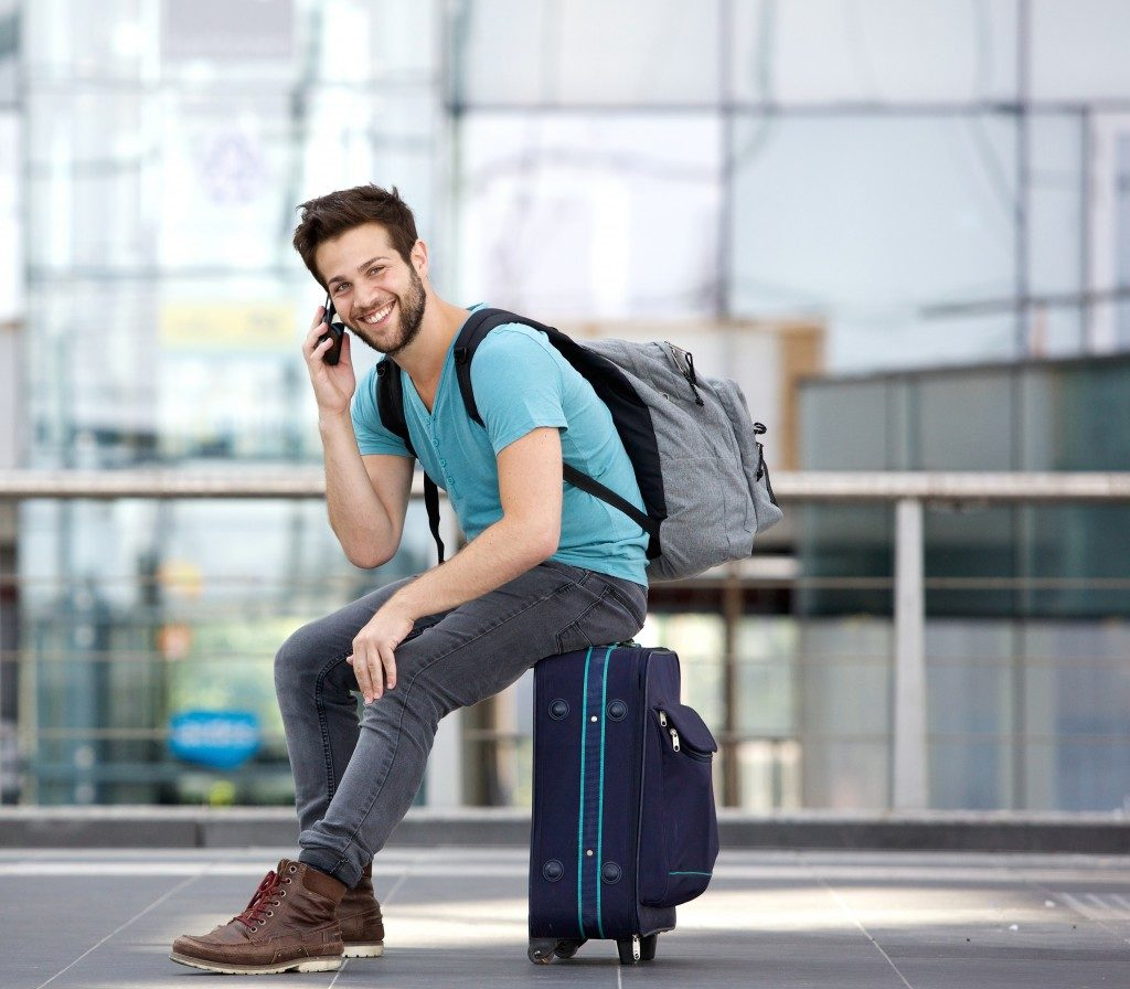 Man sitting on suitcase at airport