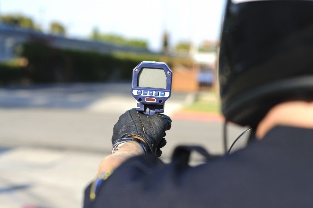 Radar gun being used by official to detect incoming car speed