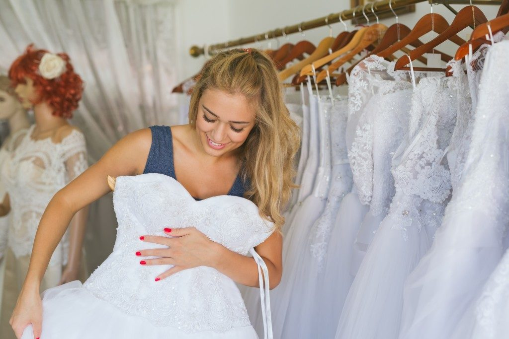 Woman choosing a wedding dress in shop
