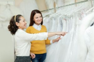 soon to be bride being assisted in shopping for her wedding gown