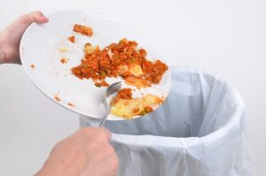 Scraping food waste from a plate into a garbage bin
