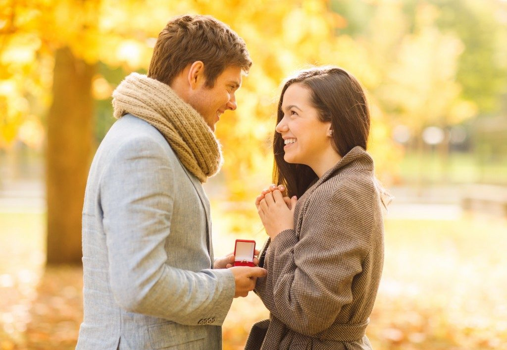Romantic man proposing to a woman in the autumn park