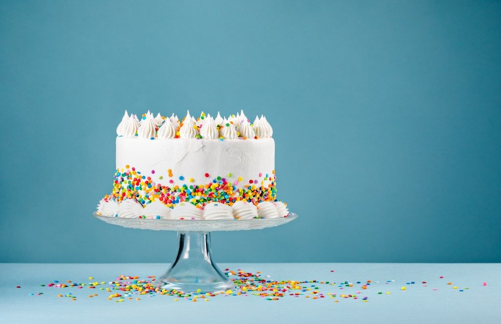 birthday cake on a stand and blue background