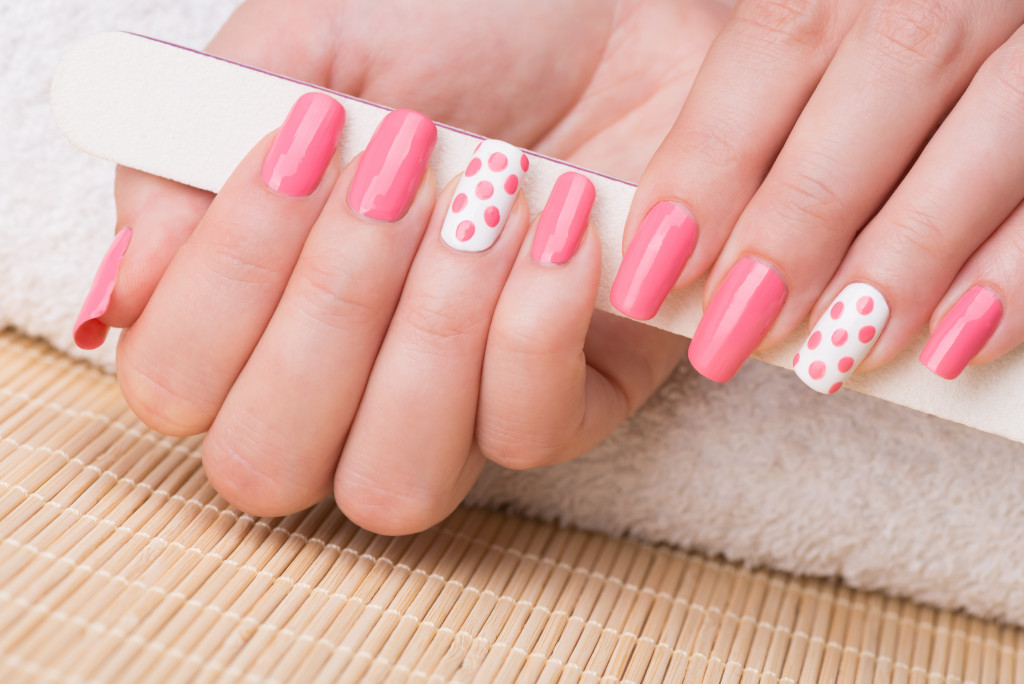 Manicure - Beauty treatment photo of nice manicured woman fingernails holding nail file