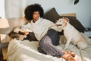 woman in bed next to her dog